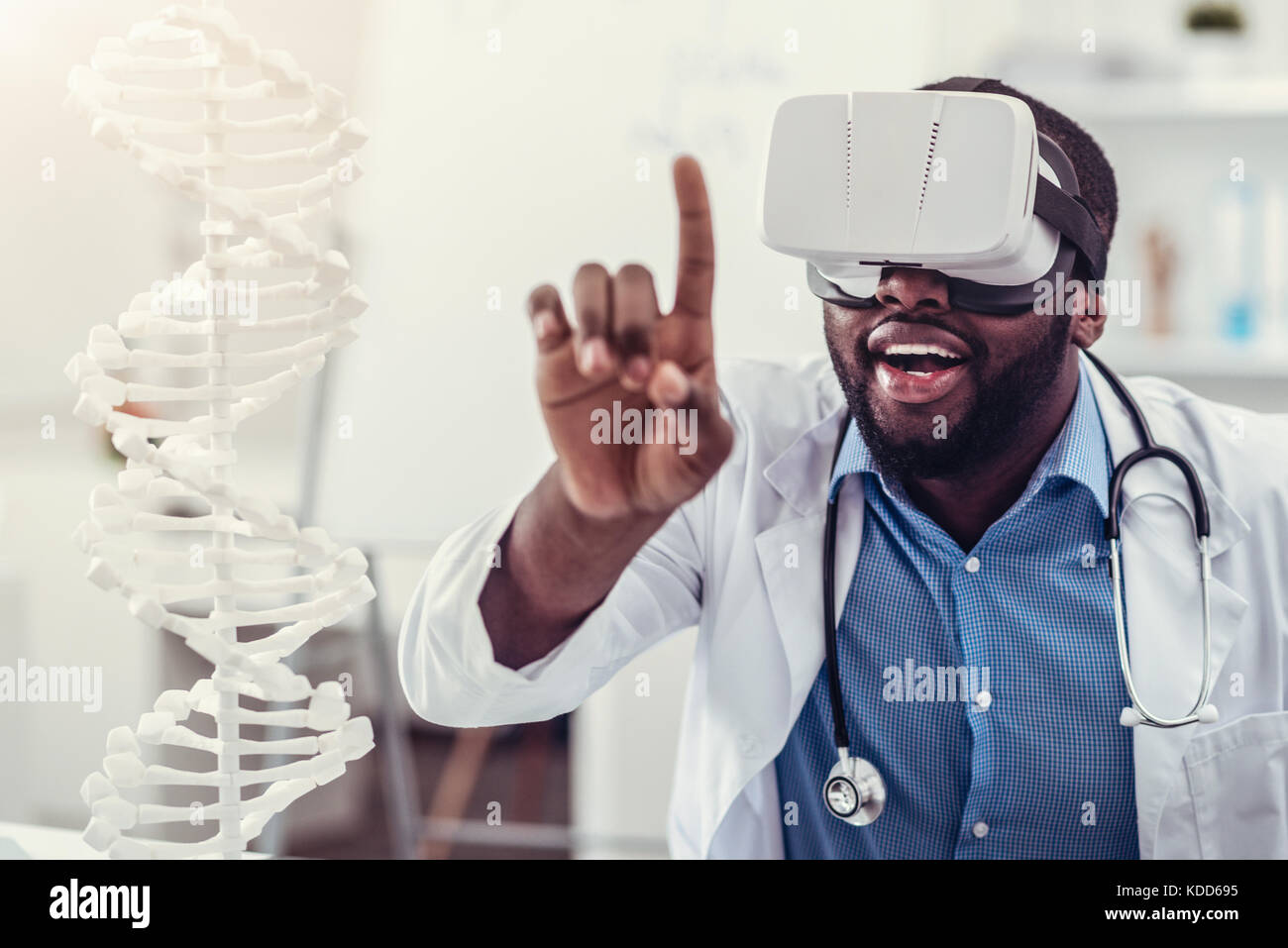 Young medical worker wearing VR goggles at work - Stock Image