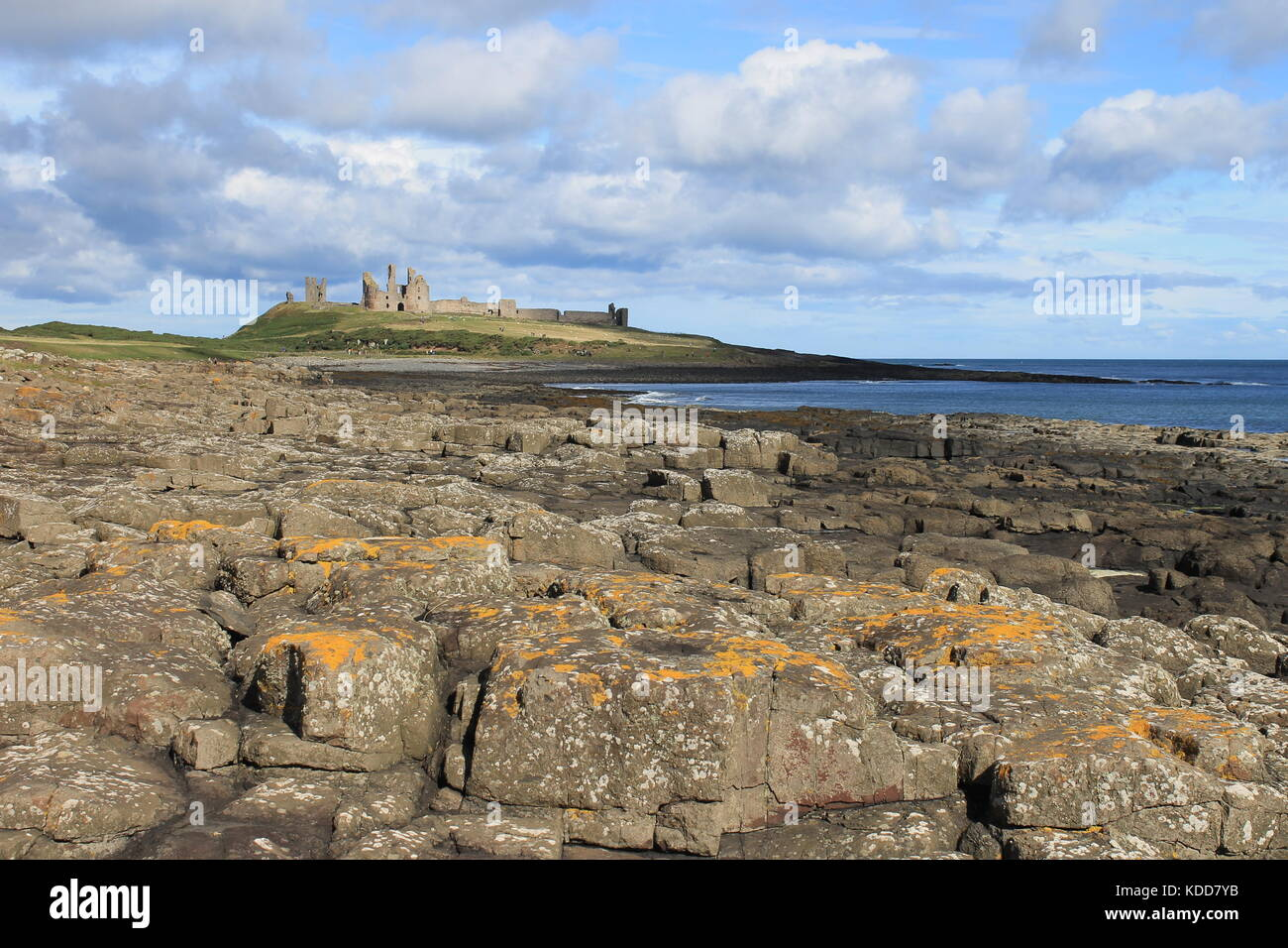 Dunstanburgh Castle and rocky foreshore of the Northumbrian coast north of Craster, Northumberland, UK - Stock Image