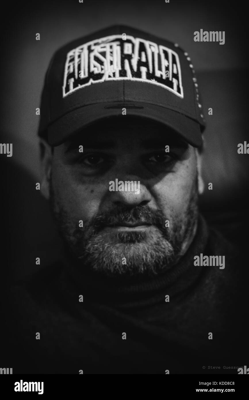 Man with cap on looking at the camera - Stock Image