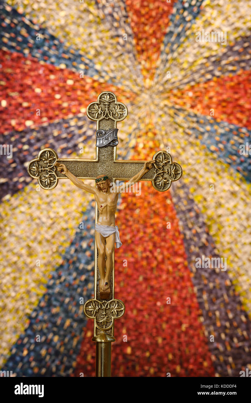Processional cross of Jesus of Nazareth King of the Jews on brass standard with starburst mosaic tile backdrop in - Stock Image