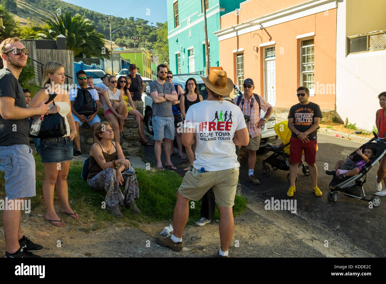 A group of visitors enjoying a free walking tour while exploring Bo Kaap, Cape Town, South Africa - Stock Image