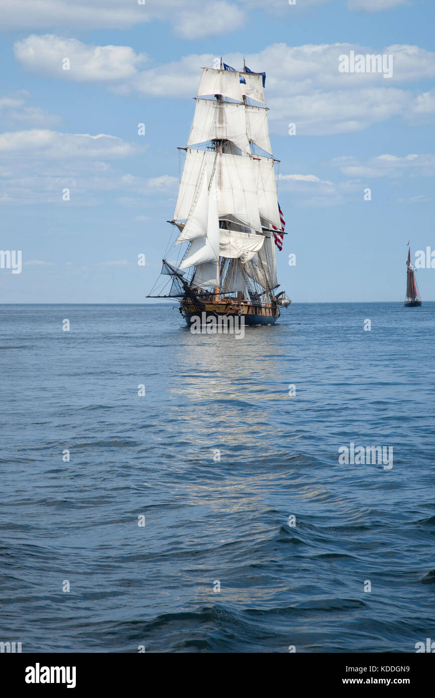 A tall ship known as a brigantine sails on blue water - Stock Image