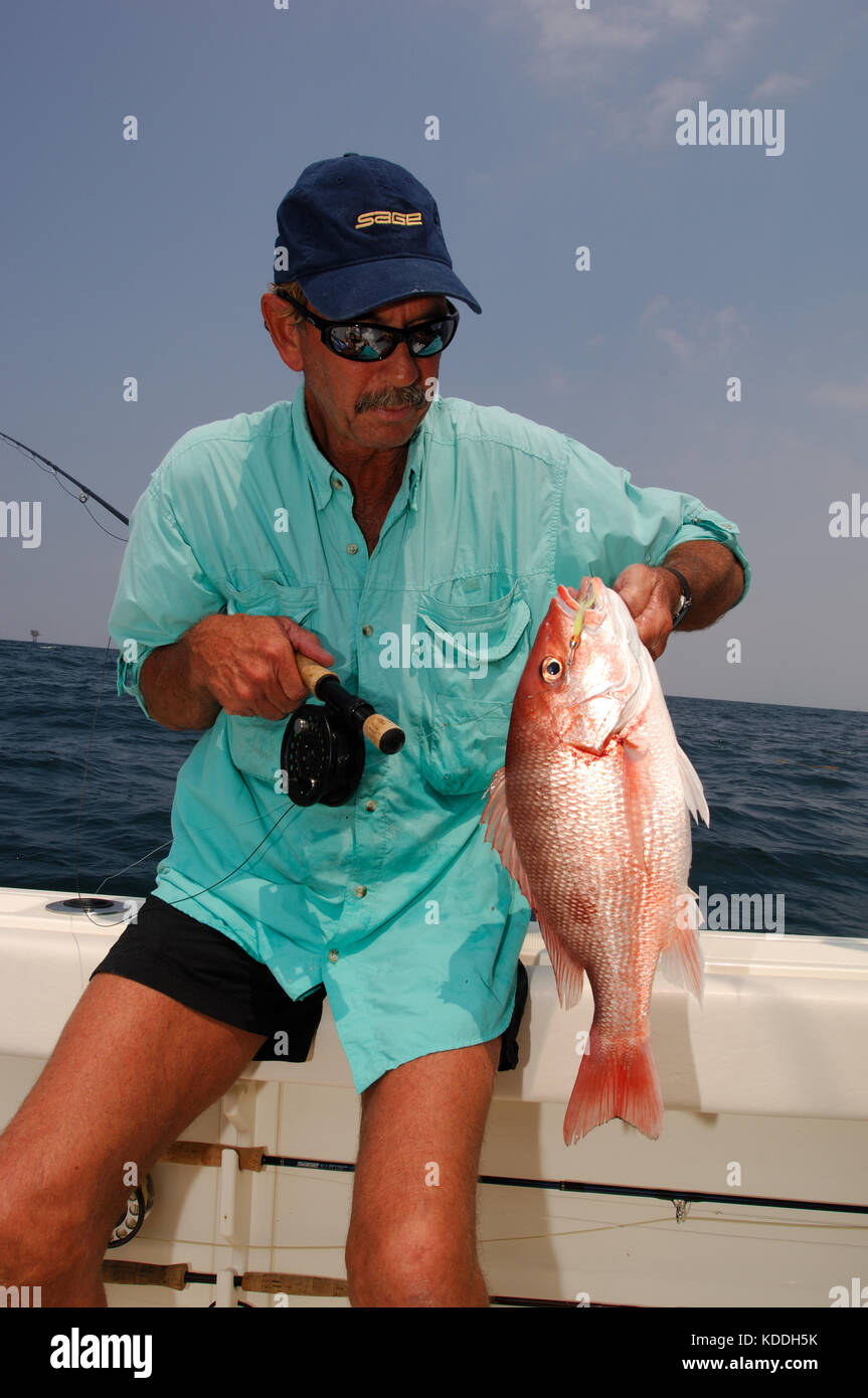A fly fisherman holds a red snapper caught while fly fishing offshore from Freeport Texas Stock Photo