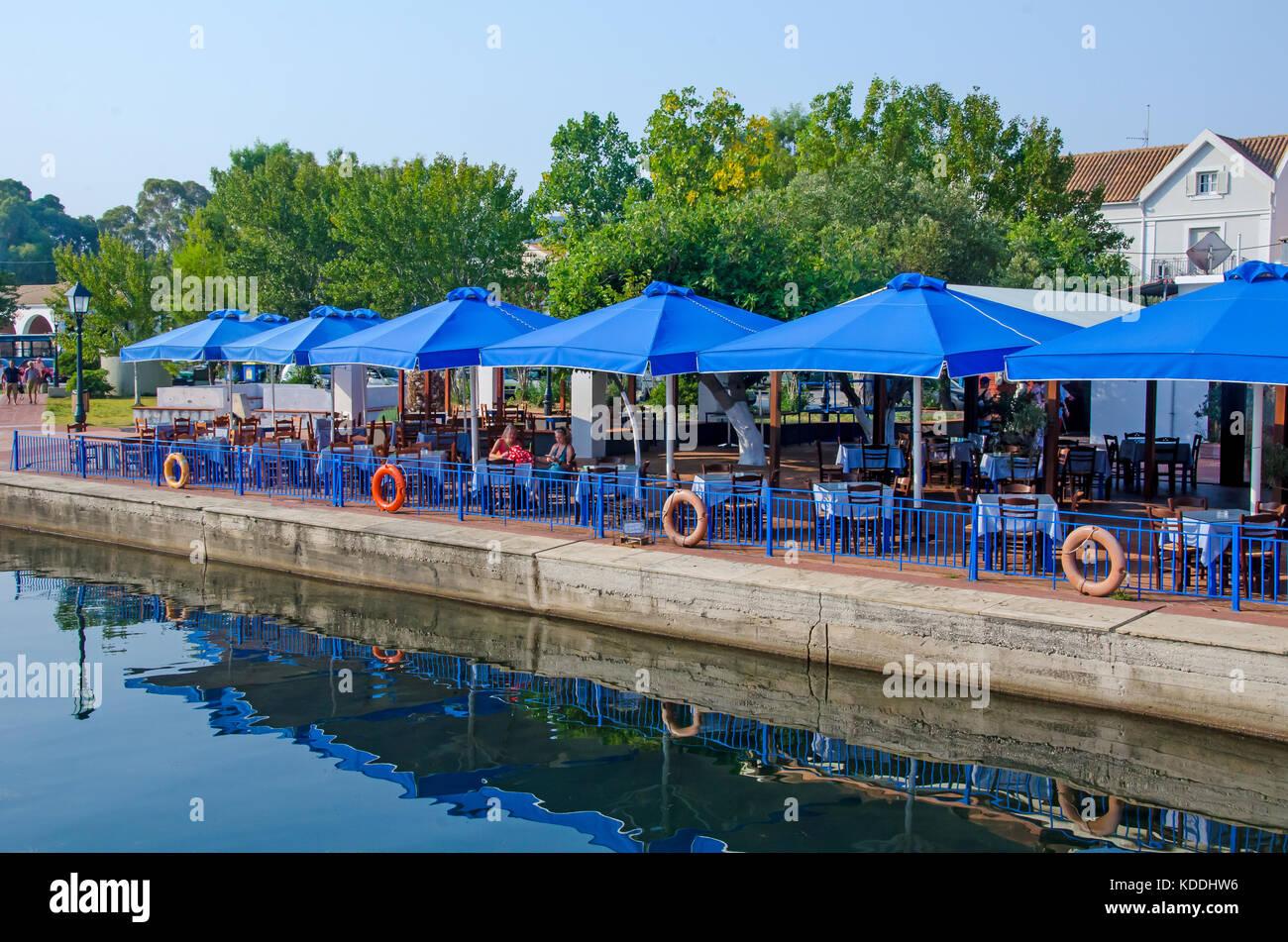 Argostoli Greece waterfront seaside cafe blue umbrellas Kefalonia, Cephalonia, Ionian Islands, Greece - Stock Image