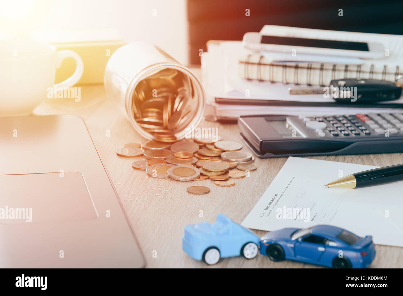 Car insurance concept:Car claim form with car toy crash on desk with Money flow out of jar coin bank ,warm tone - Stock Image