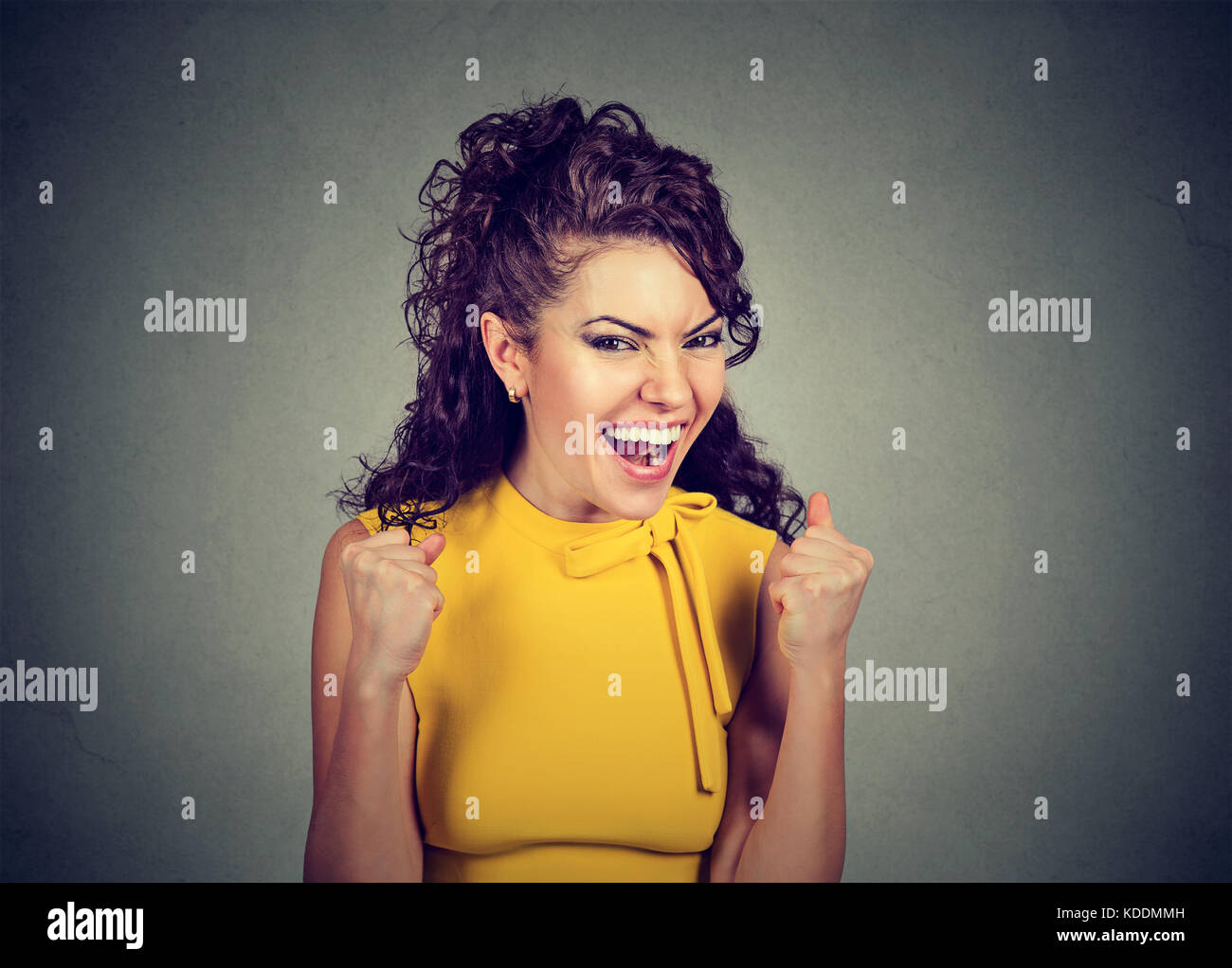 Happy winner. Woman exults pumping fists celebrates success on gray wall background - Stock Image