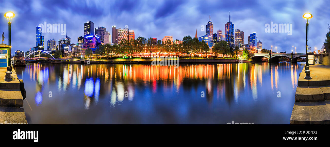 180 degrees panorama of Melbourne city CBD from South Yarra with reflection of bright morning city lights in still - Stock Image