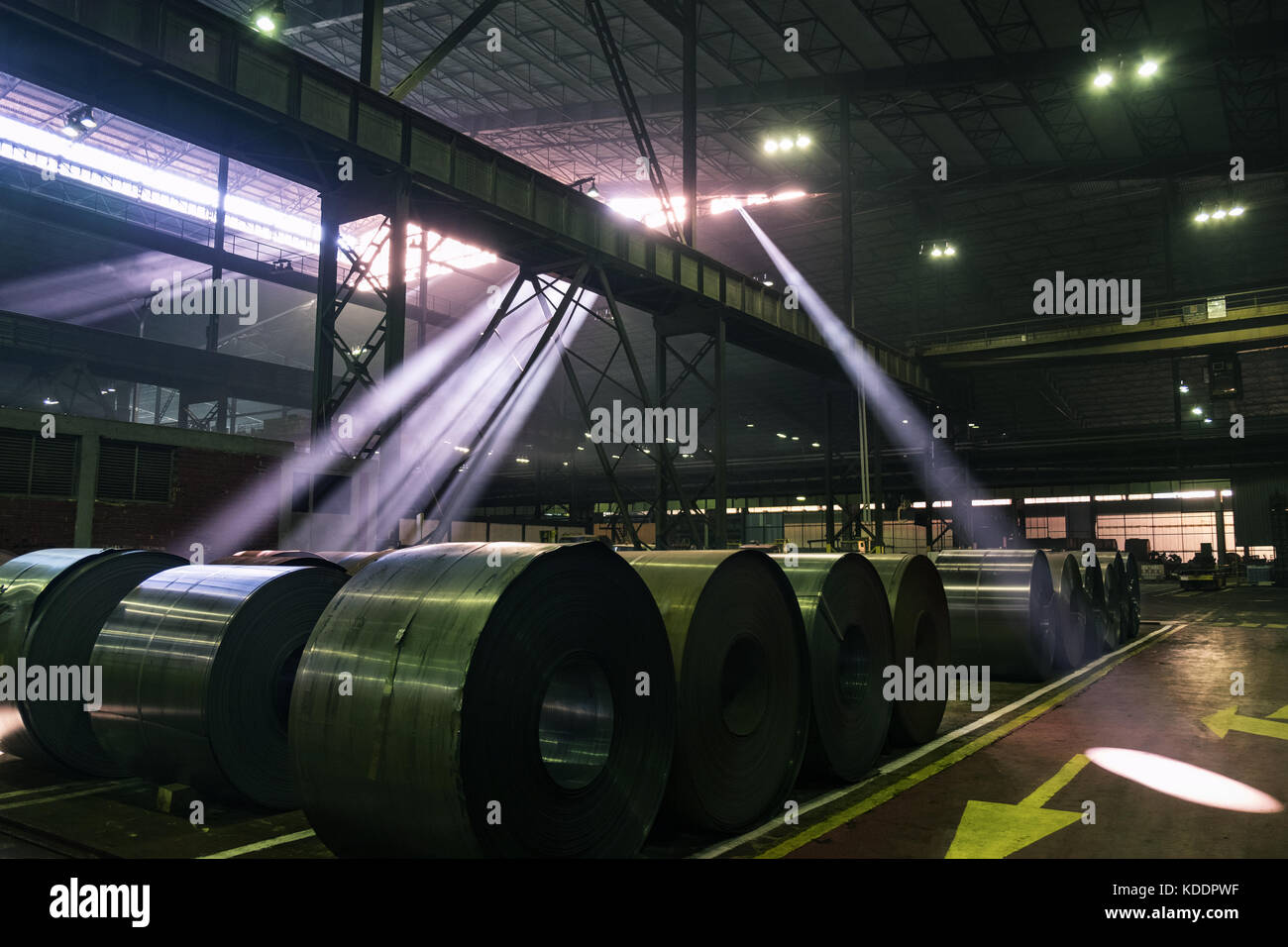 Sun beams bursting through the roof windows of a steel mill shining on steel coils - Stock Image