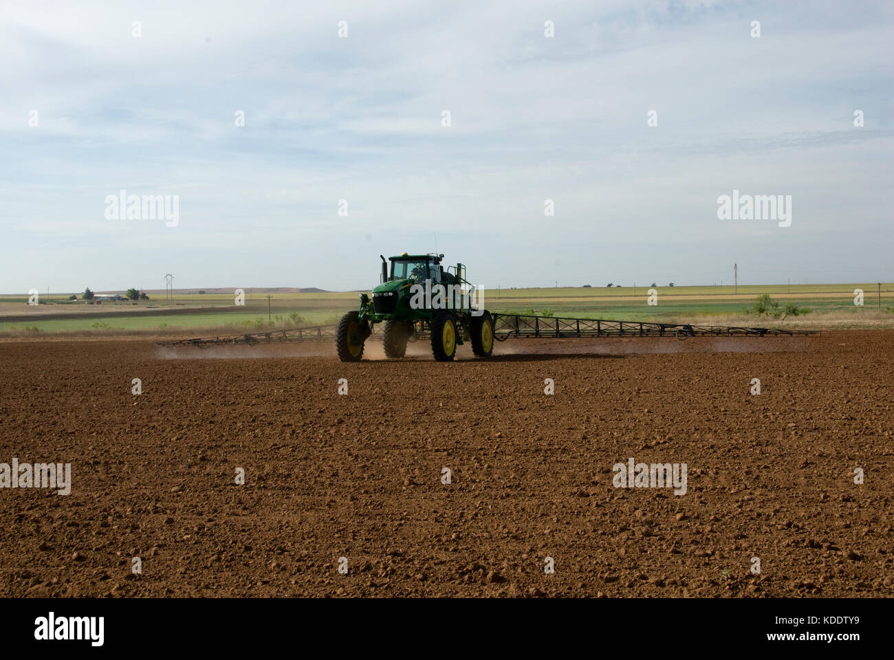 JOHN DEERE TRACTOR SPRAYING PLOWED GROUND WITH PRE-EMERGE HERBICIDE - Stock Image