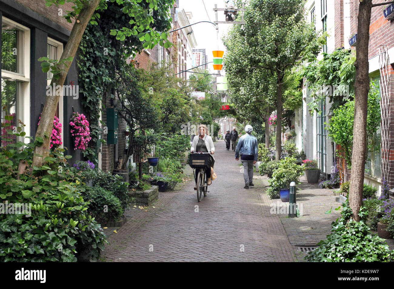 Pedestrians and a cyclist share a narrow traffic-free street in Haarlem city centre, North Holland. - Stock Image
