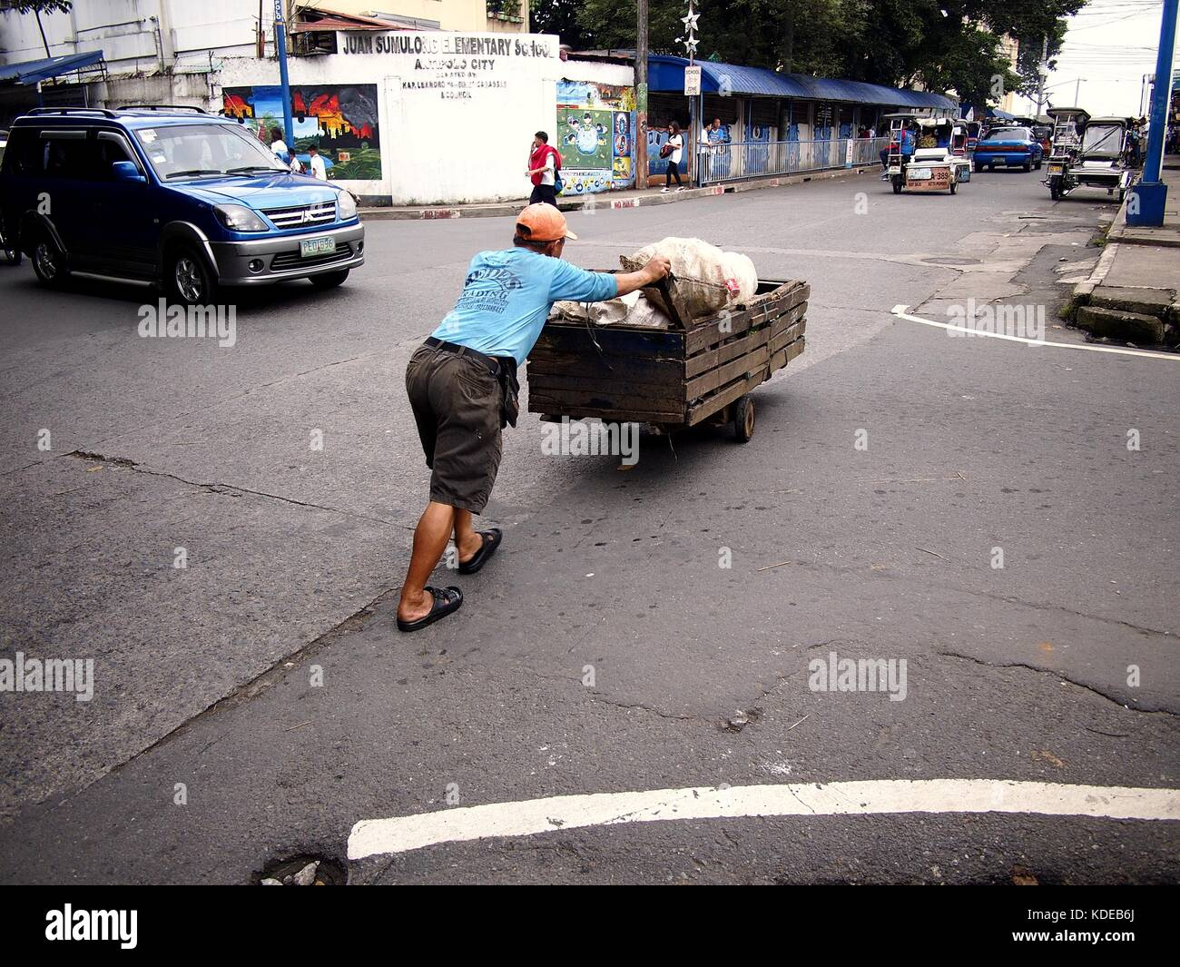 ANTIPOLO CITY, PHILIPPINES - OCTOBER 9, 2017: A recyclable materials collector pushes his wooden cart across a street. - Stock Image