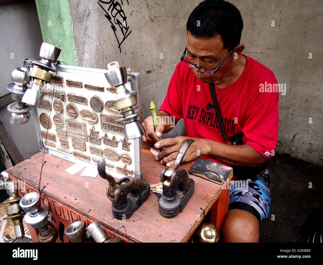 ANTIPOLO CITY, PHILIPPINES - OCTOBER 12, 2017: A locksmith and stamp maker creates a stamp pad for a customer at - Stock Image