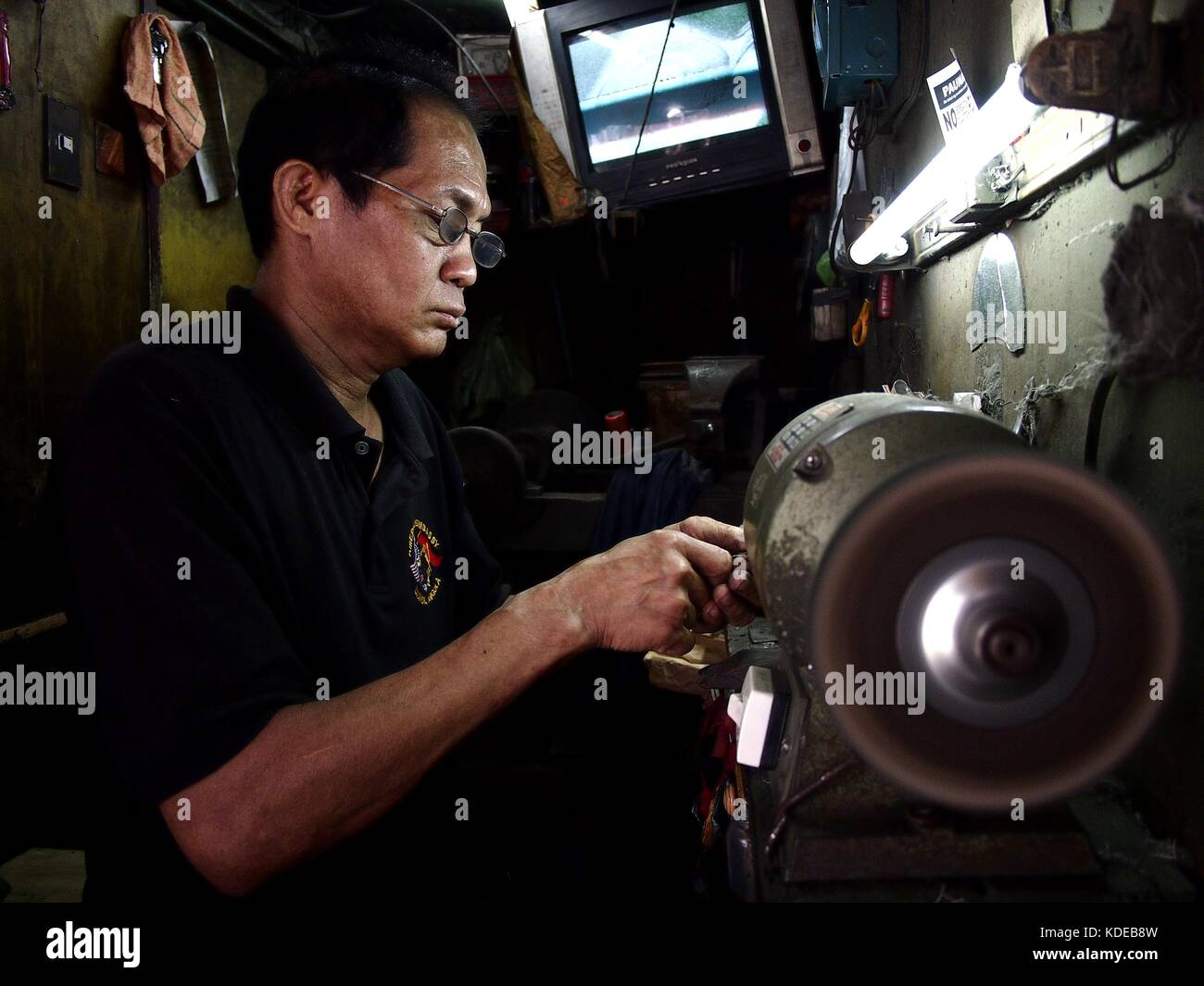 ANTIPOLO CITY, PHILIPPINES - OCTOBER 12, 2017: A worker sharpens a nipper for a customer at his makeshift stall - Stock Image