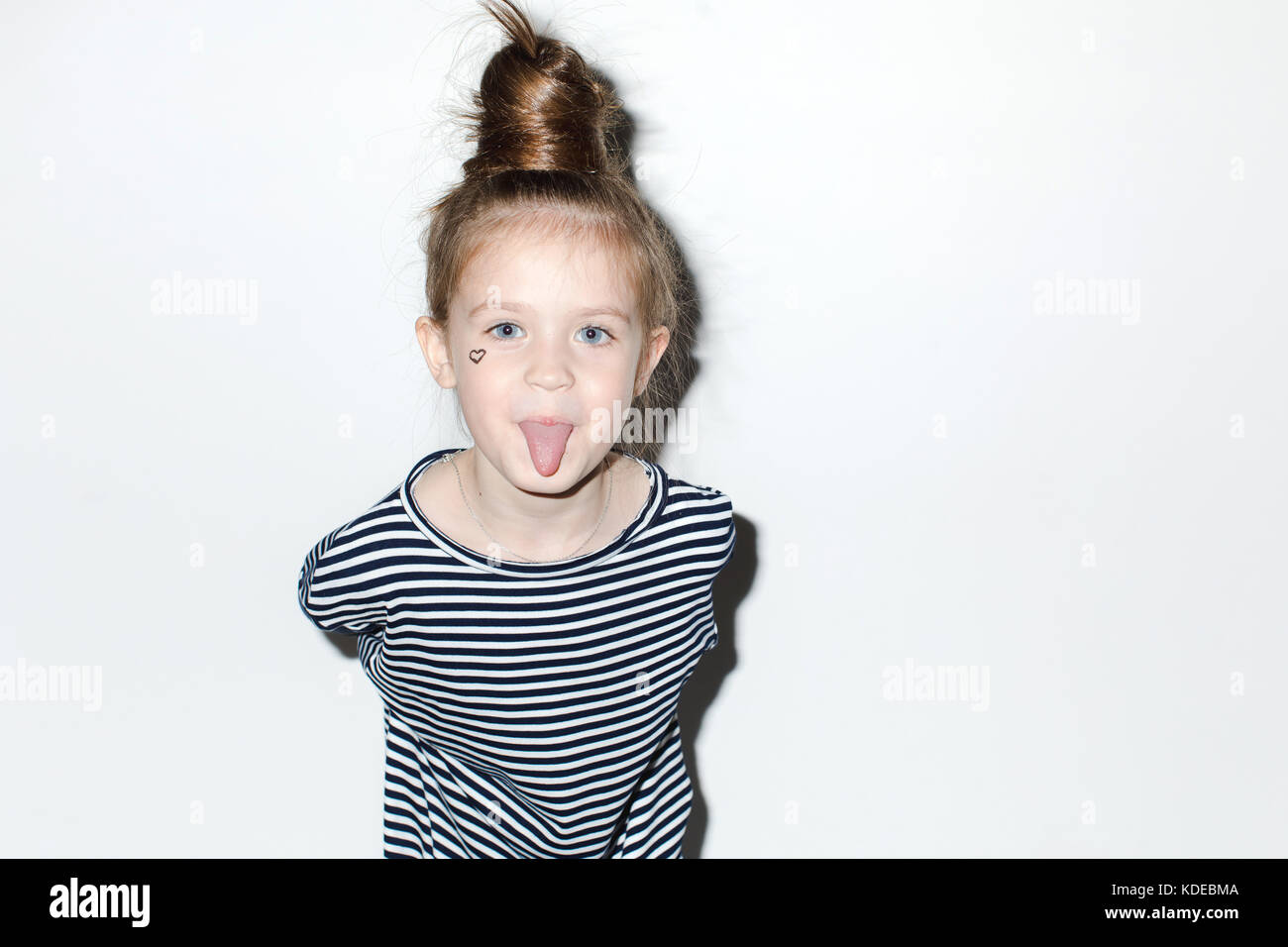 Cute girl showing tongue on a white background - Stock Image