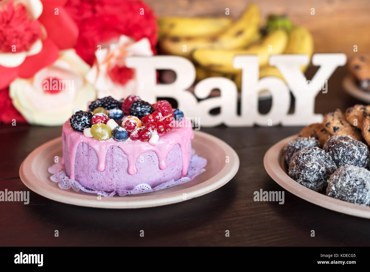 Birthday cake and muffins with wooden greeting sign on dark background. Wooden sing with letters Baby and holiday - Stock Image