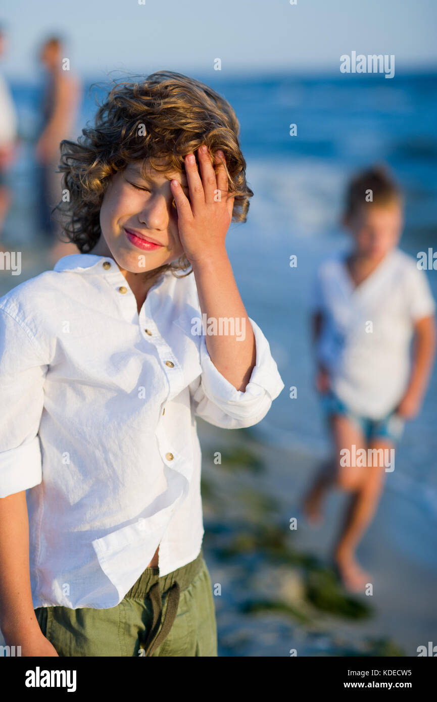 Portrait of boy of 10-11 years against the background of the rough sea. He covers eyes with a palm from the blinding - Stock Image