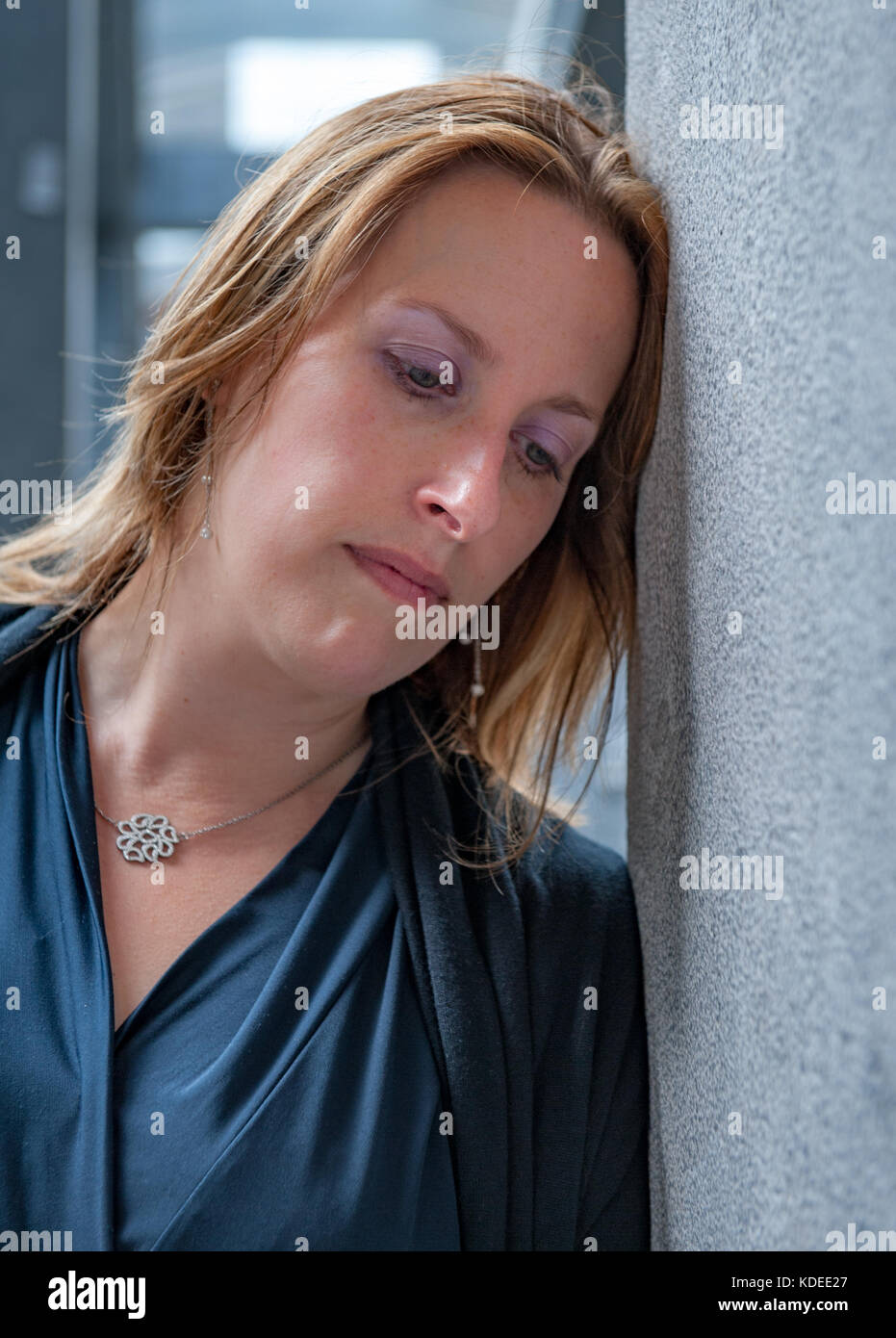 Woman resting her head against a wall - Stock Image