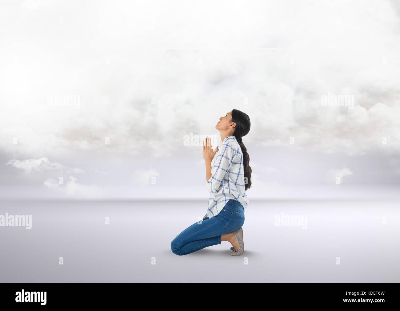 Digital composite of Woman praying under clouds - Stock Image