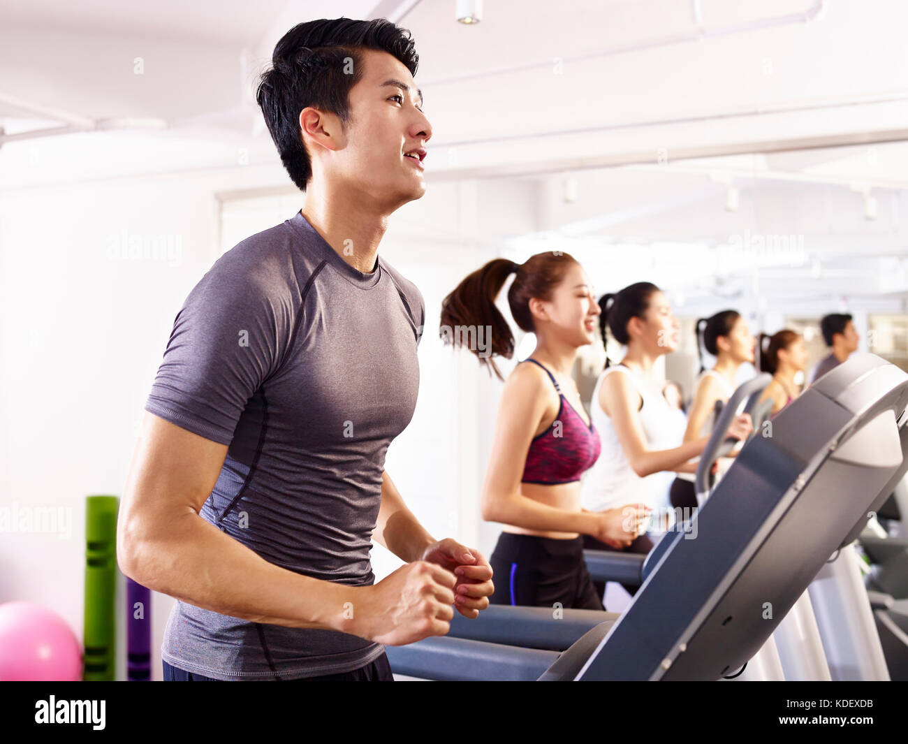 young asian adult working out on treadmill. - Stock Image