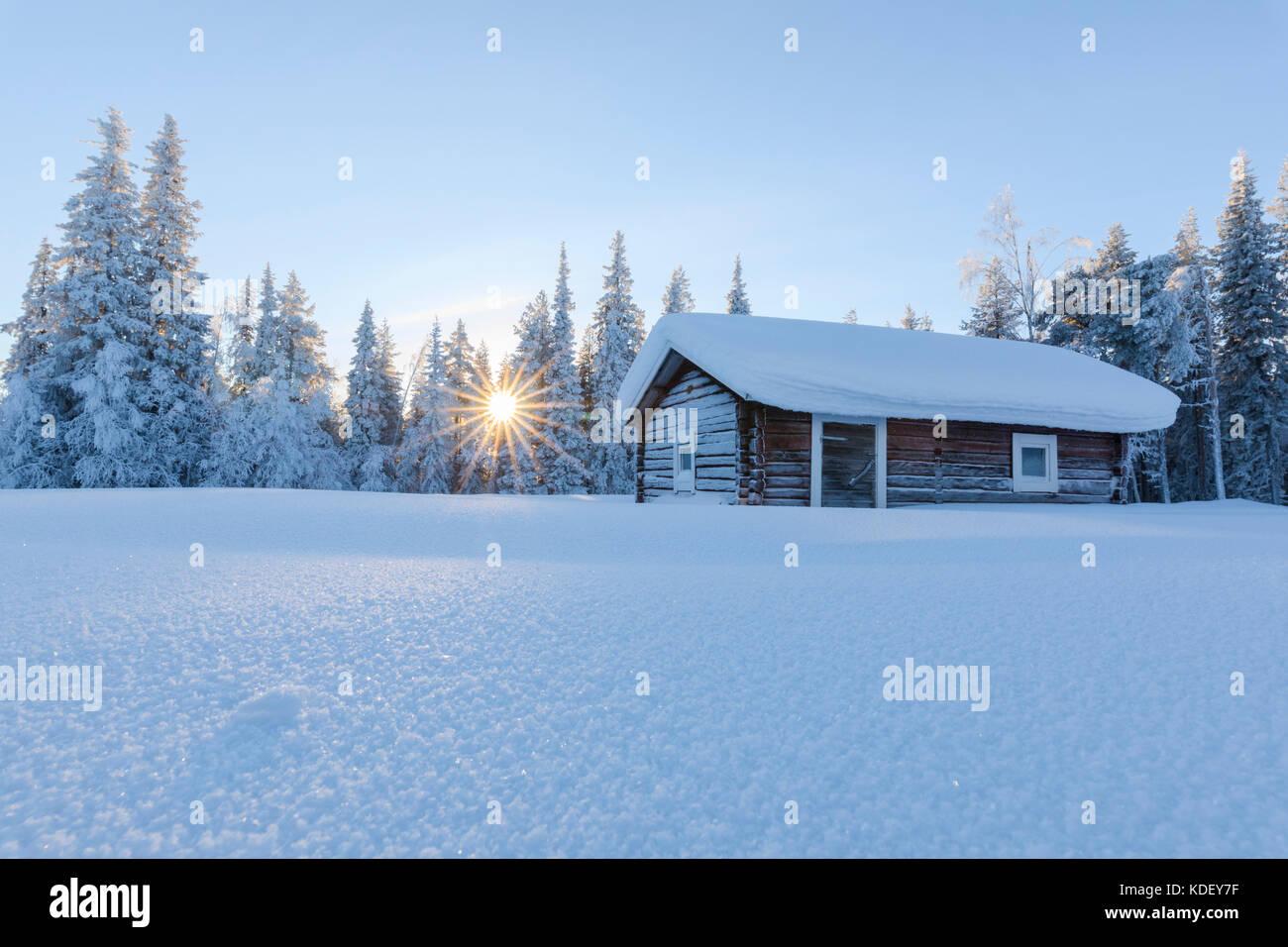 Sunburst on wooden hut covered with snow, Kiruna, Norrbotten County, Lapland, Sweden Stock Photo