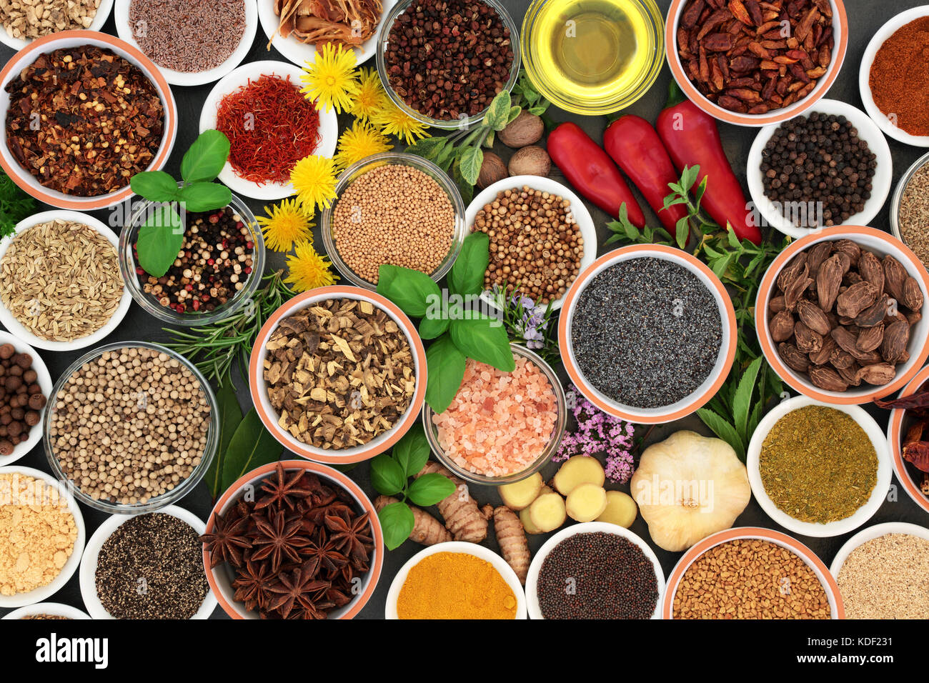 Fresh and dried herbs and spices in bowls and loose forming a colourful abstract background. Top view. - Stock Image