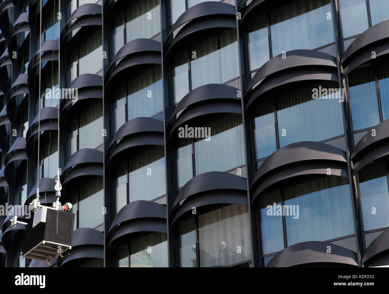 window cleaner on a tower building in barcelona - Stock Image