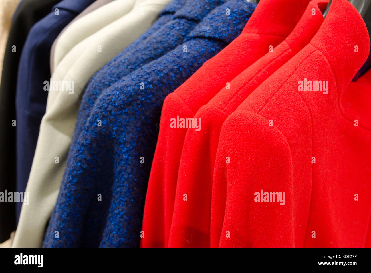 womens cashmere coats of different colors in the store - Stock Image