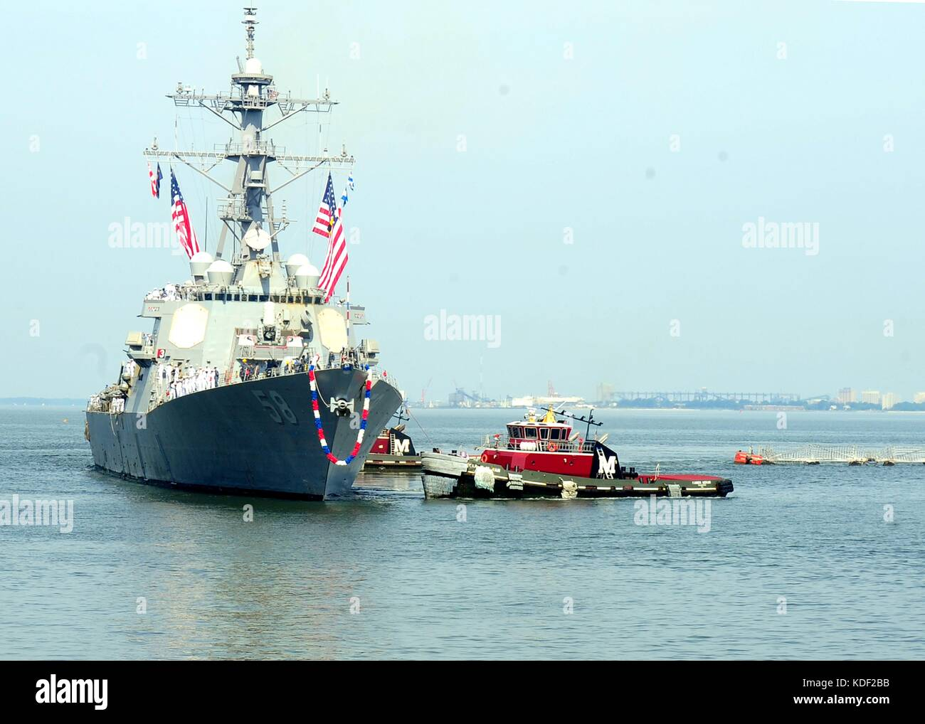 Tugboats help tow the U.S. Navy Arleigh Burke-class guided-missile destroyer USS Laboon as it returns to its homeport - Stock Image