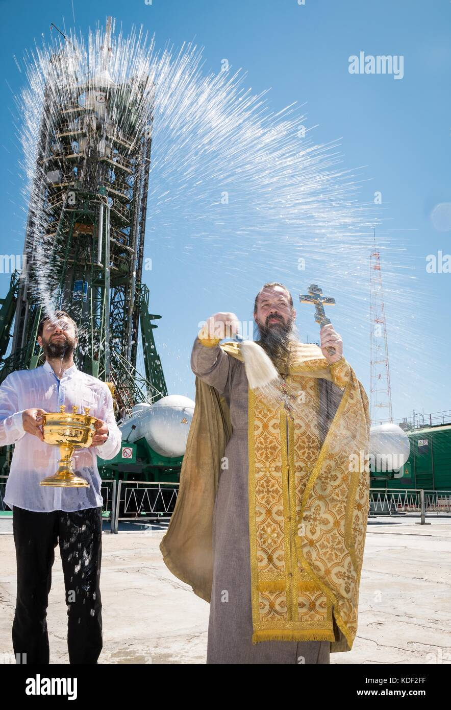 An Orthodox Priest blesses the Soyuz MS-05 spacecraft during a traditional pre-launch ceremony at the Baikonur Cosmodrome - Stock Image