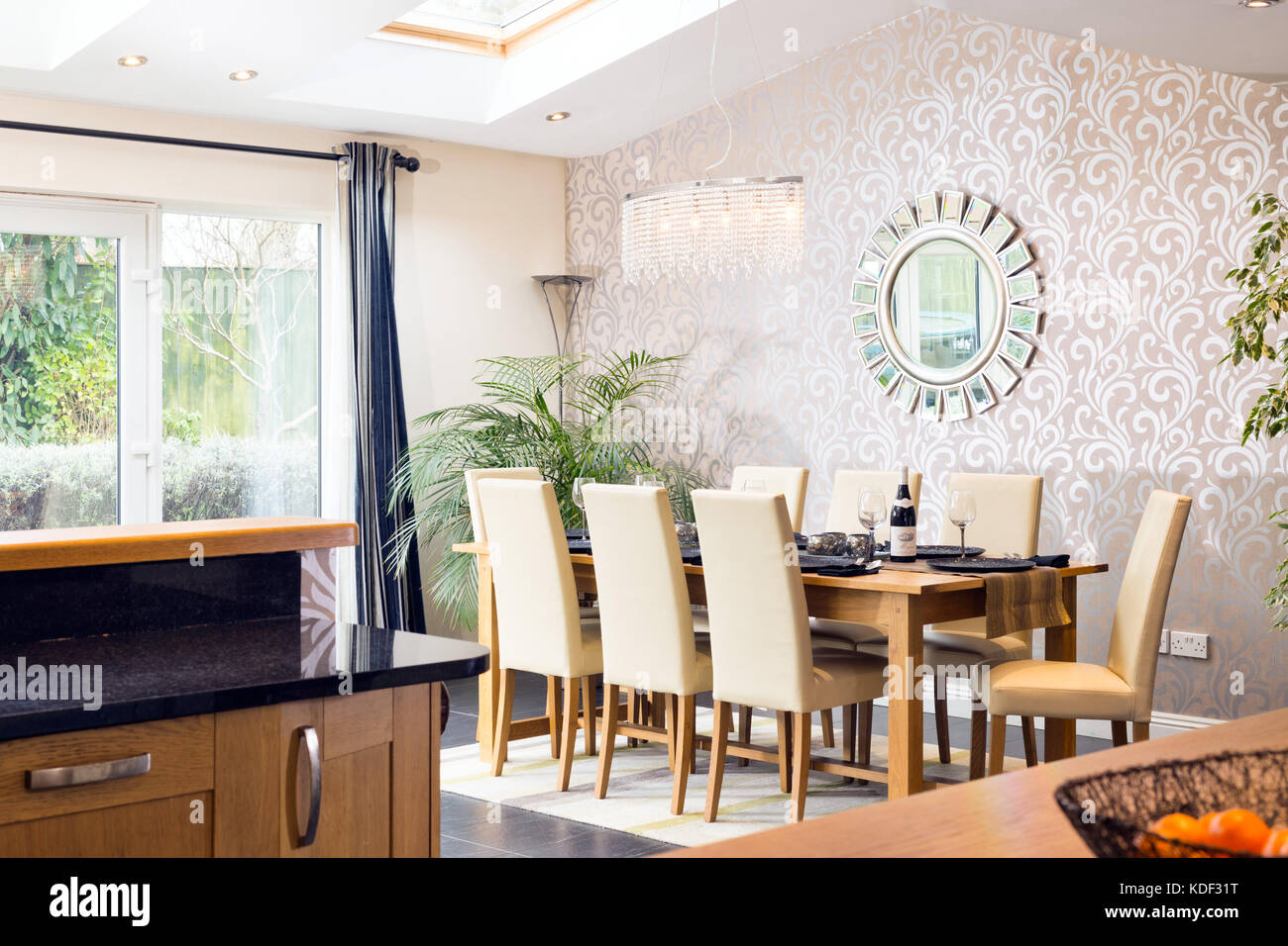The dining area, showing a table & chairs in a single story rear extension. Viewed from the home's kitchen. - Stock Image