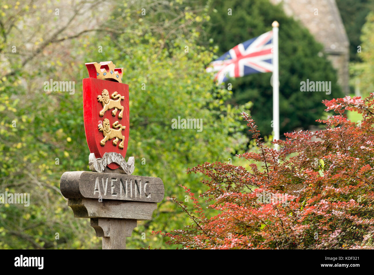 The sign in the centre of the historic Cotswold village of Avening, Glocestershire, UK. Between Autumnal trees with - Stock Image