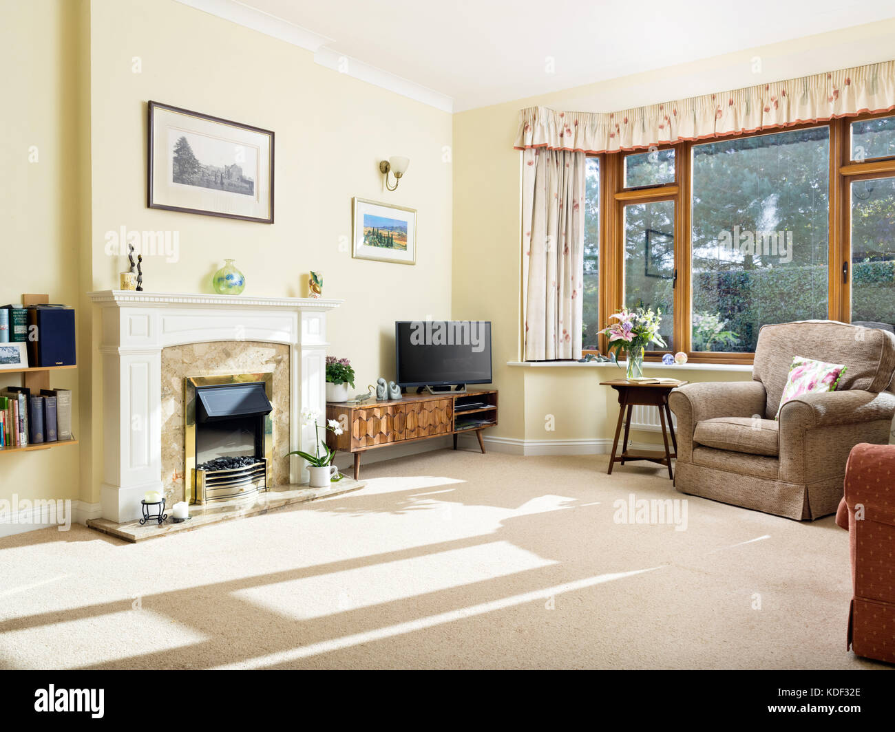 A dated, furnished, sunny living room with fireplace in a home Stock ...