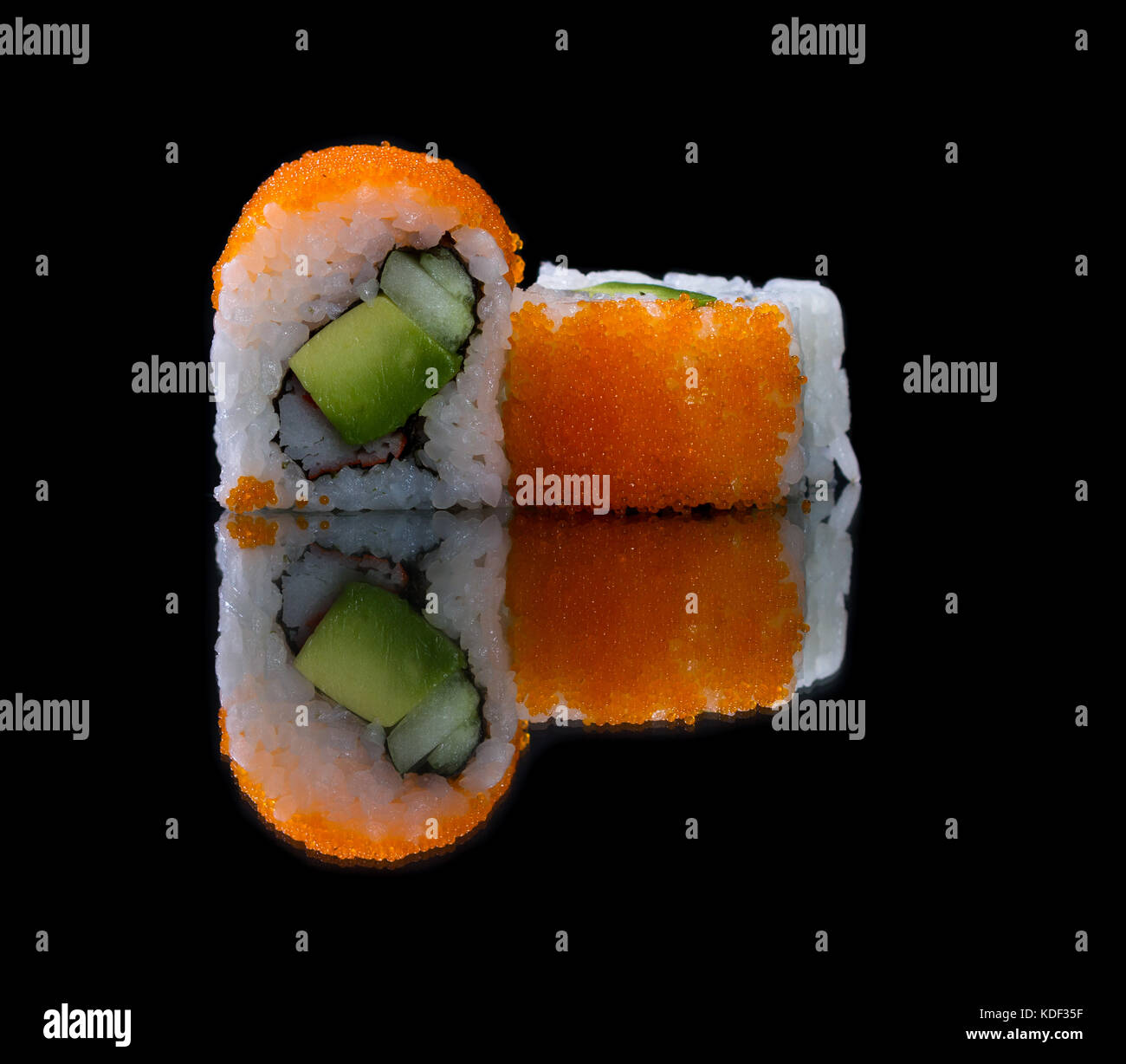 close up of a piece of sushi with glowing and colorful fish eggs on top - Stock Image