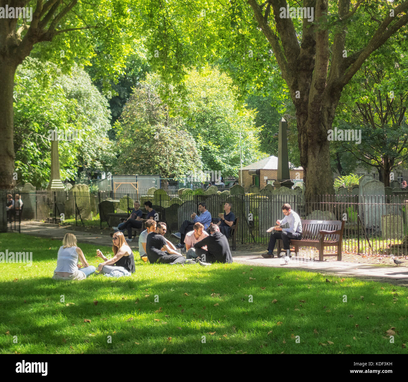 BUNHILL FIELDS BURIAL GROUND, LONDON, UK:  Office Workers enjoying lunch in Bunhill Fields which is now a Public - Stock Image