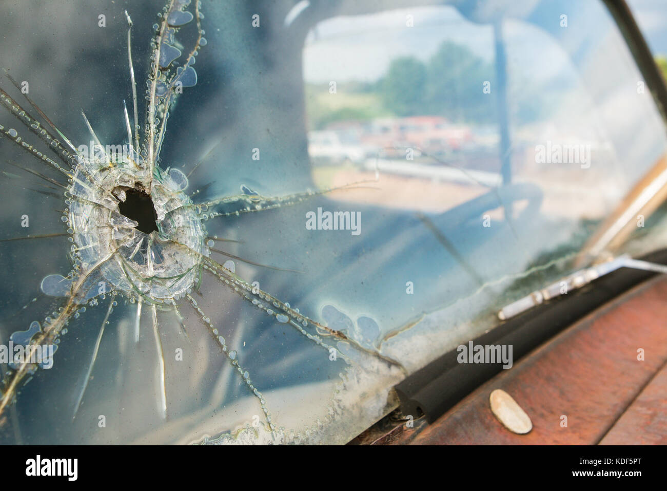 The windshield of a junkyard vehicle is cracked and splintered from what appears to be a bullet hole - Stock Image
