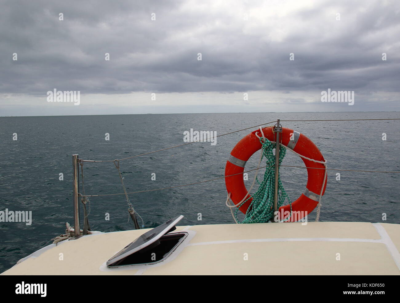 View of the open ocean from the deck of a yacht on a blustery cloudy day in landscape format with copy space - Stock Image