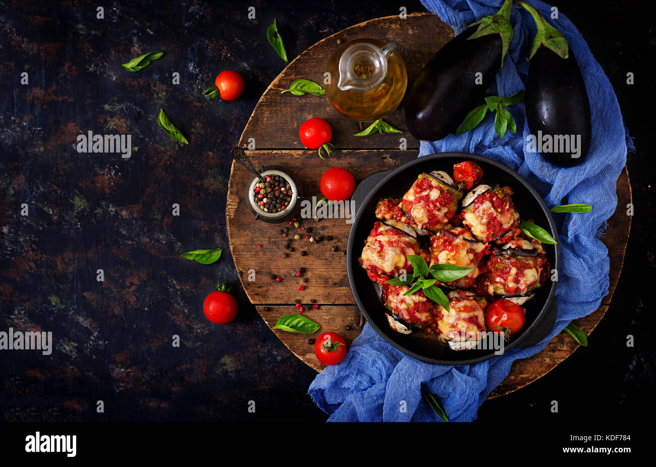 Eggplant (aubergine) rolls with meat in tomato sauce. Flat lay. Top view - Stock Image
