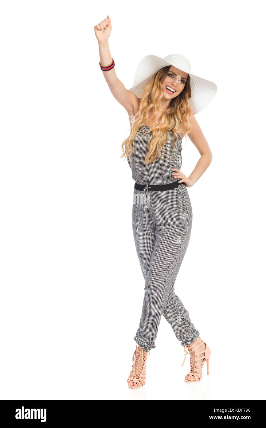 Happy beautiful young woman in dotted jumpsuit, white hat and high heels is standing with legs crossed, rising hand - Stock Image