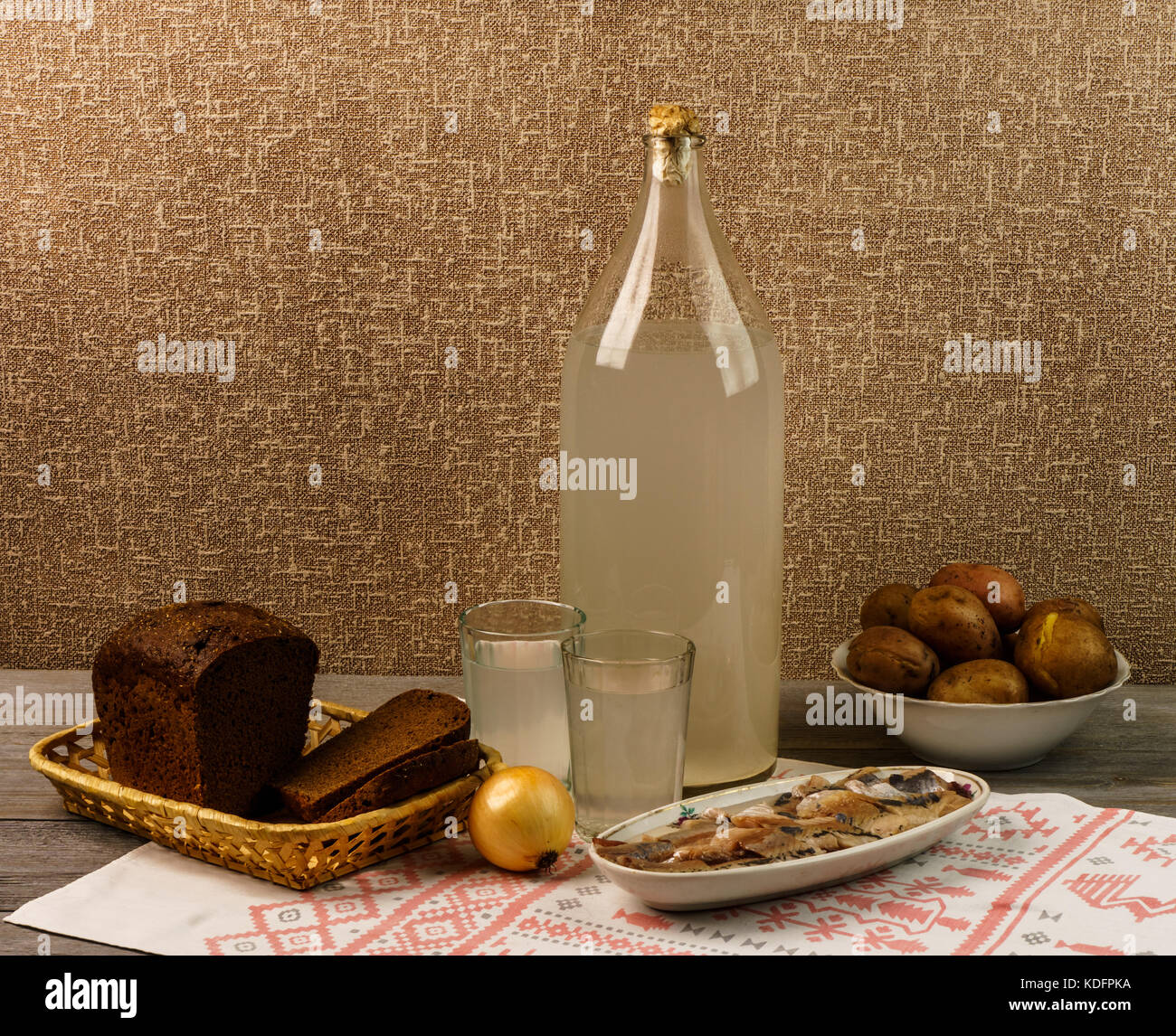 Ukrainian national drink and snack. The bottle and glass of moonshine on the old wooden table - Stock Image
