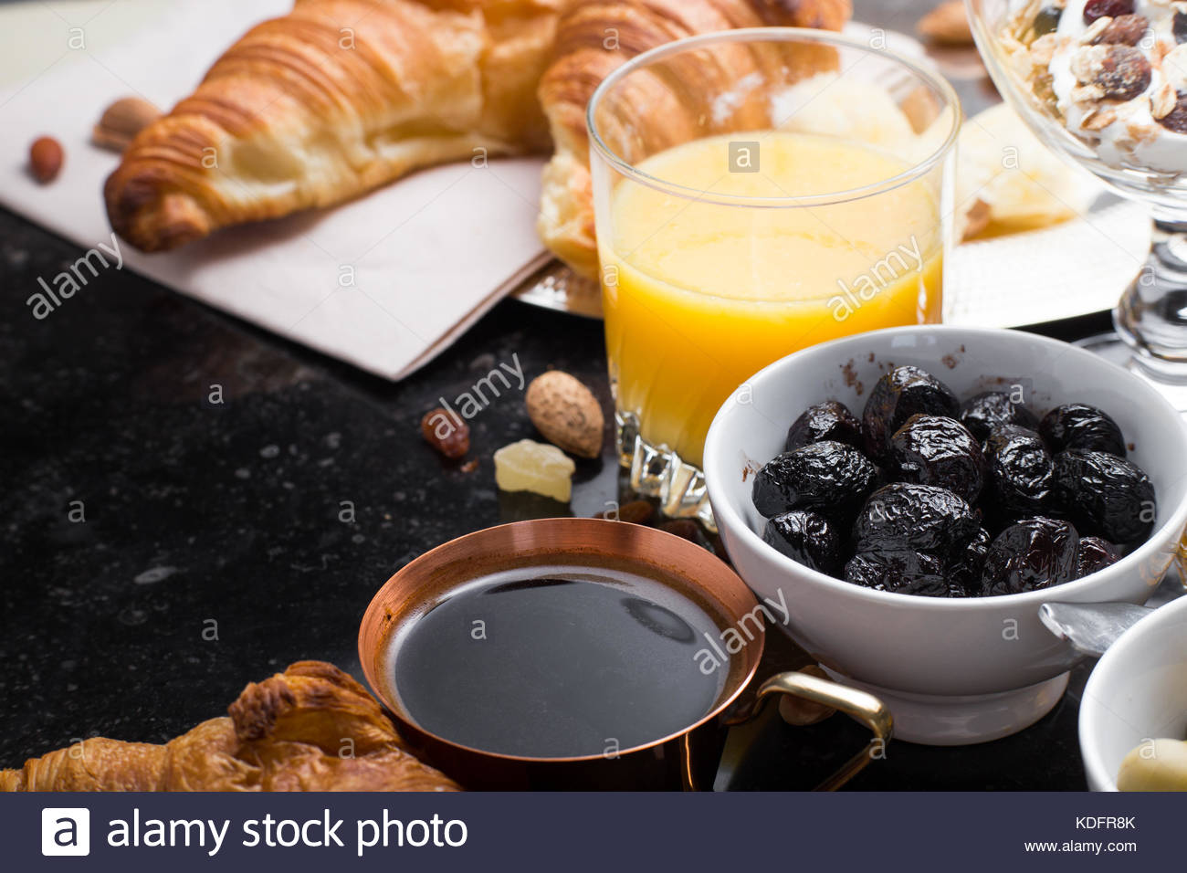 Breakfast assorted yogurt, granola, coffee, juice, croissant, olives. Appetizer mix with morning dishes. Healthy, - Stock Image