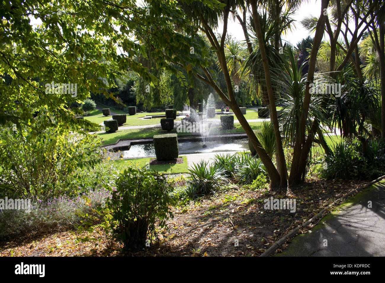 A hidden view of a beautiful garden catching the water fountain in action. - Stock Image
