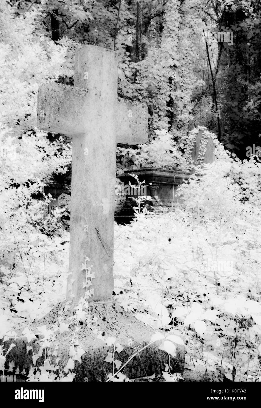 An infrared shot of an old, stone, graveyard cross. - Stock Image