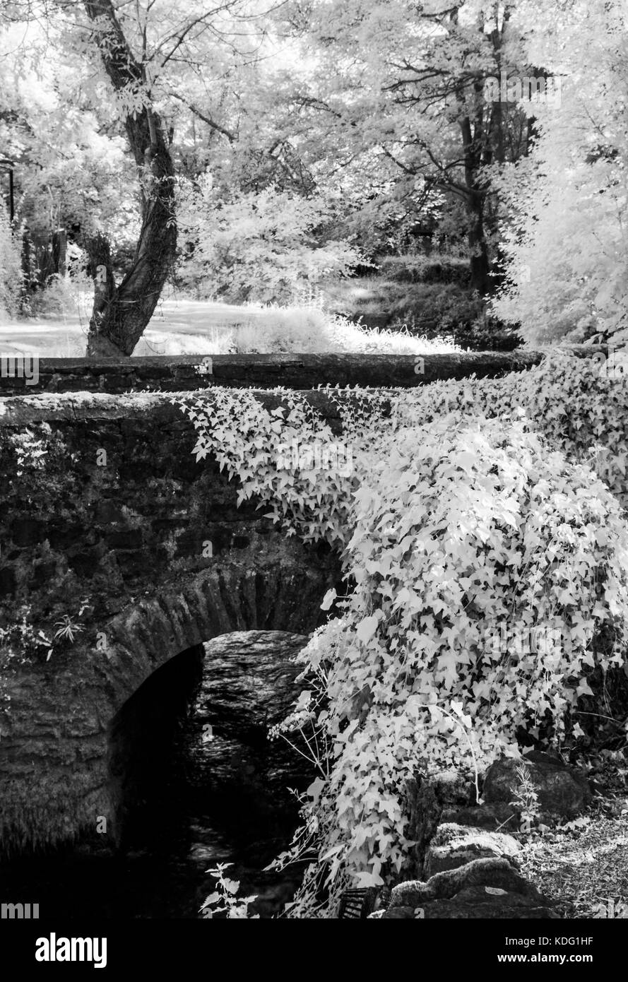 A small mill stream and stone bridge in Exmoor, Somerset shot in infrared. - Stock Image