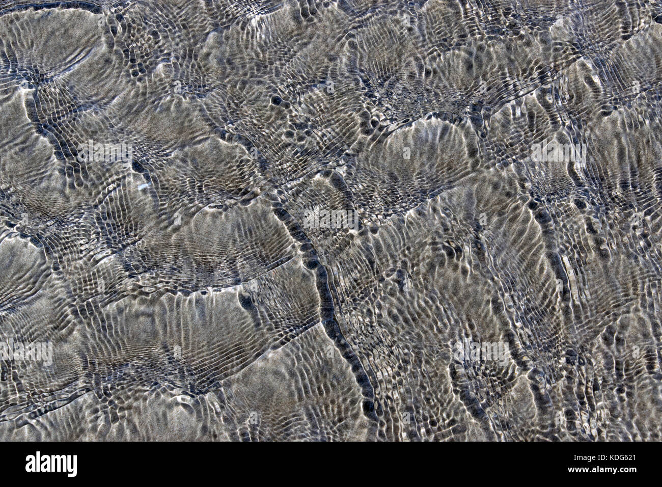 Water rippling across sand - Stock Image