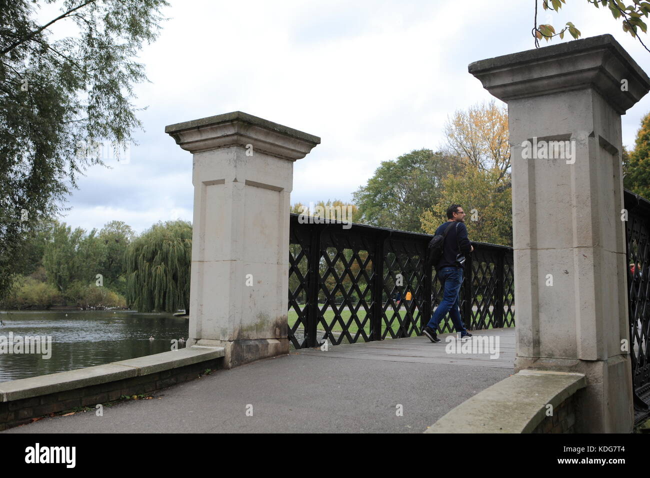 Man walks over a footbridge in Regents Park, London.  The river in the background.  England UK - Stock Image