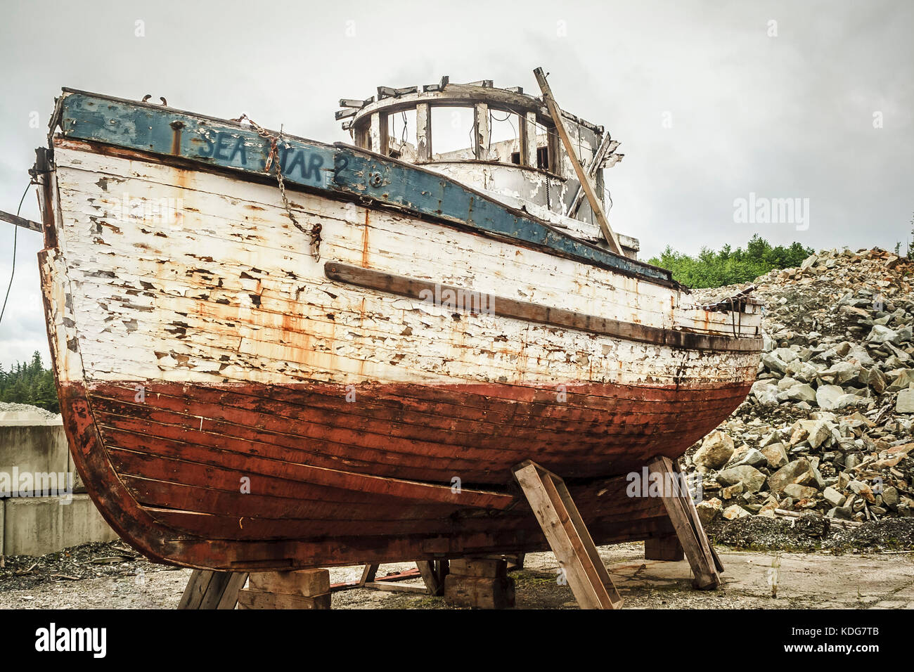 The Sea Star 2, a classic 32-foot west coast wooden fish boat, stands in ruins at the shipyard at Shearwater (British - Stock Image