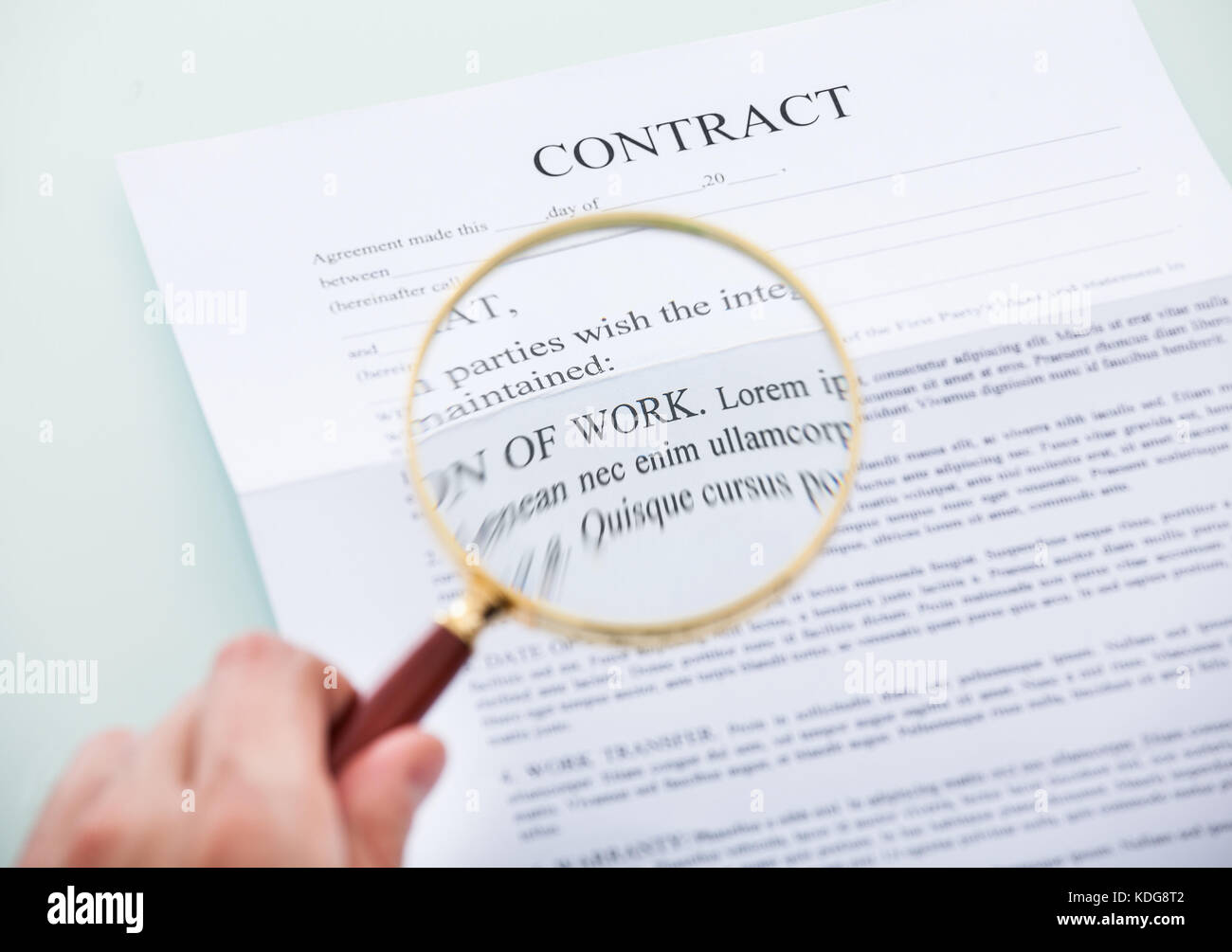 Close-up Of Person's Hand Looking At Contract Through Magnifying Glass - Stock Image