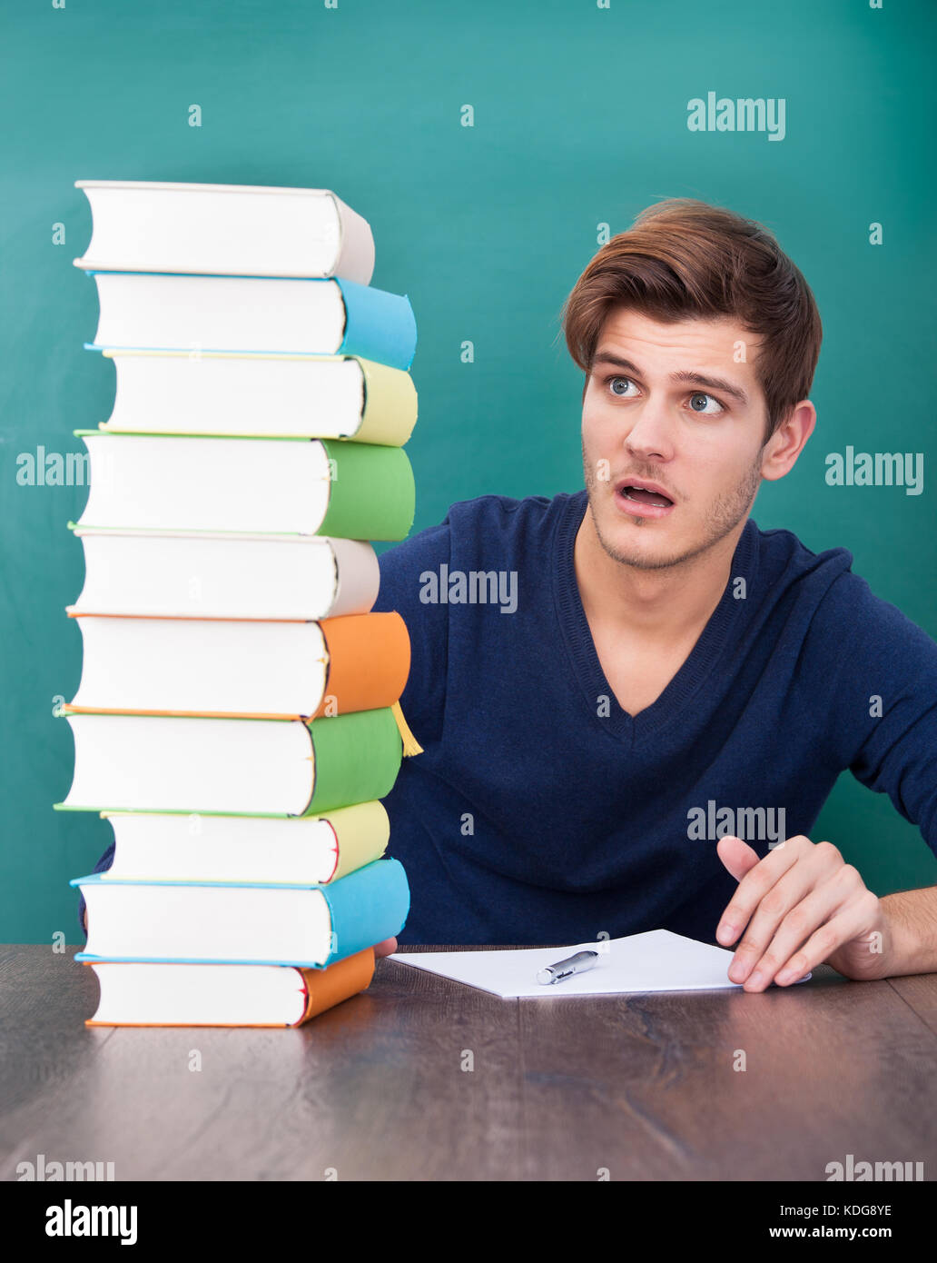 Portrait Of A Shocked Male Student Looking At Stack Of Books - Stock Image