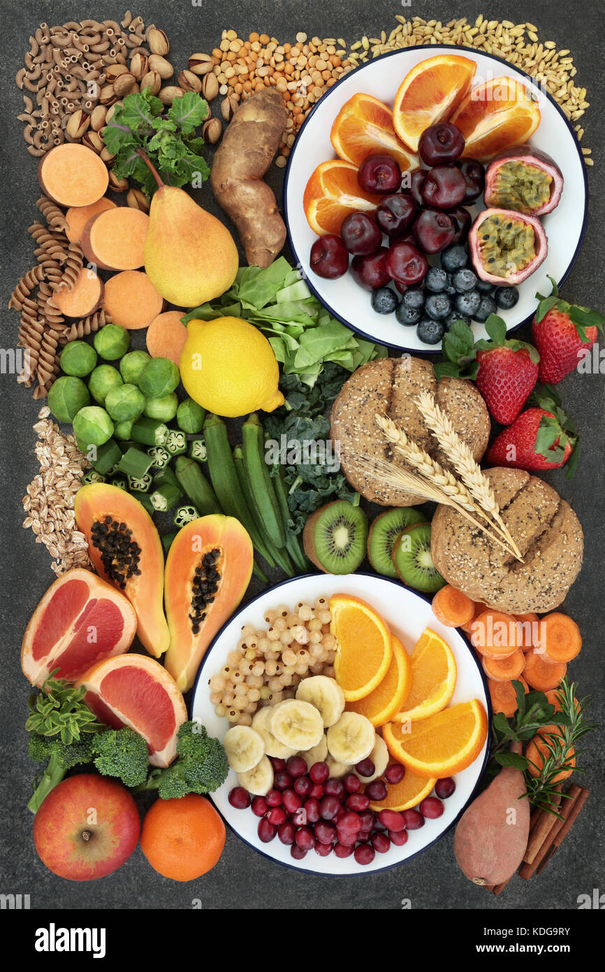 Healthy high fiber dietary food concept with fruit, vegetables, legumes, nuts, spice, cereals, whole wheat pasta - Stock Image