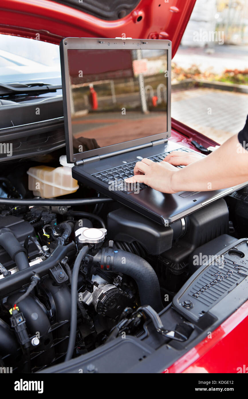 Close-up Of Hand Typing On A Computer In A Garage - Stock Image